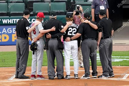 Umpire Joe West, third from left, poses for photos his fellow umpires, St. Louis Cardinals manager Mike Shildt (8) and Chicago White Sox manager Tony La Russa before a baseball game, in Chicago. West set a record of 5,376 games when he worked Tuesday night's game