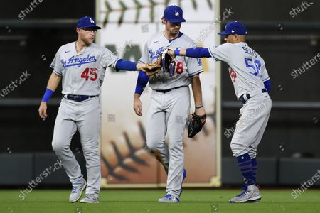 Los Angeles Dodgers' Matt Beaty (45), DJ Peters, center, and Mookie Betts celebrate the team's win over the Houston Astros in a baseball game, in Houston