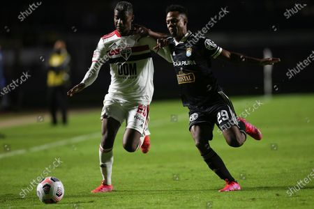 Luis Orejuela of Brazil's Sao Paulo, left, and Nilson Loyola of Peru's Sporting Cristal battle for the ball during a Copa Libertadores soccer match at Morumbi stadium in Sao Paulo, Brazil