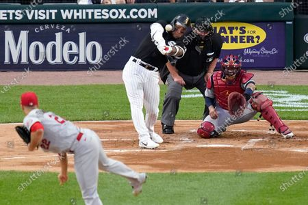Chicago White Sox's Yoan Moncada hits a sacrifice fly off St. Louis Cardinals starting pitcher Jack Flaherty during the first inning of a baseball game, in Chicago. Moncada's sacrifice advanced Tim Anderson to third