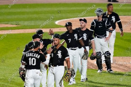 Chicago White Sox's Yoan Moncada (10), Jose Abreu, right, front, and teammates celebrate the team's 8-3 win over the St. Louis Cardinals in a baseball game, in Chicago