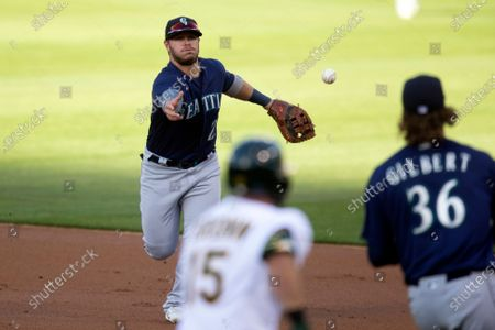 Seattle Mariners first baseman Ty France (23) flips the ball to pitcher Logan Gilbert (36) to put out Oakland Athletics' Seth Brown (15) at first base during the first inning of a baseball game, in Oakland, Calif