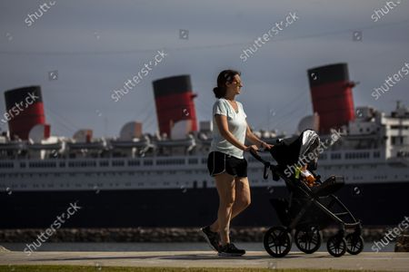A woman walks with a stroller along Shoreline Aquatic Park, with the Queen Mary ship in the distance, docked in Long Beach, CA, photographed Tuesday, May 25, 2021. The ship has been a tourist destination and hotel for years and is now in danger of capsizing according to a recent inspection report. (Jay L. Clendenin / Los Angeles Times)