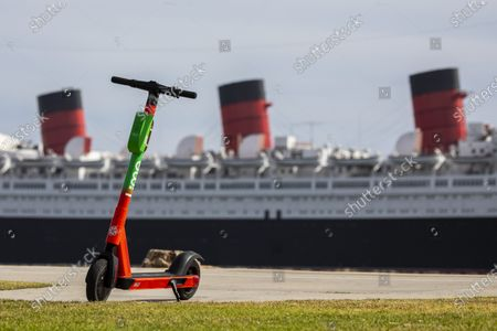 A scooter is seen in the foreground in Shoreline Aquatic Park, across from the Queen Mary ship docked in Long Beach, CA, photographed Tuesday, May 25, 2021. The ship has been a tourist destination and hotel for years and is now in danger of capsizing according to a recent inspection report. (Jay L. Clendenin / Los Angeles Times)