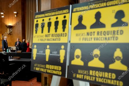"""Signs requiring masks if not vaccinated against Covid-19 are displayed as Francis Collins, director of the U.S. National Institutes of Health (NIH), from left, Senator Roy Blunt, a Republican from Missouri and ranking member of the Senate Appropriations Subcommittee on Labor, Health and Human Services, Education, Anthony Fauci, director of the National Institute of Allergy and Infectious Diseases, and Diana Bianchi, director of the Eunice Kennedy Shriver National Institute of Child Health and Human Development, speak following a Senate Appropriations Subcommittee hearing in Washington, D.C., U.S.,. The hearing is titled """"National Institutes of Health's FY22 Budget and the State of Medical Research."""""""