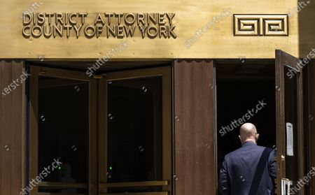 Stock Image of A person enters a courthouse building with a sign for the District Attorney of the County of New York in New York, New York, USA, 26 May 2021. It was revealed on 25 May that Manhattan District Attorney Cyrus R. Vance Jr. has reportedly convened a grand jury to hear evidence collected as a result of a two-year long investigation by Vance's office into potential criminal acts by former US President Donald Trump, the Trump Organization, and executives at the company.