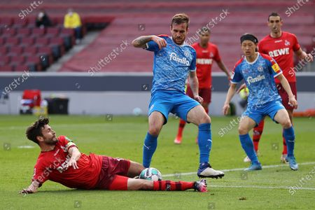 Jonas Hector (L) of Koeln battles for possession with Marco Komenda of Kiel during the German Bundesliga relegation play-off, first leg soccer match between 1. FC Koeln and Holstein Kiel in Cologne, Germany, 26 May 2021.