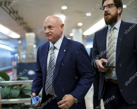 Sen. Mark Kelly, D-Ariz., arrives as senators rush to the chamber for votes ahead of the approaching Memorial Day recess, at the Capitol in Washington, . Lawmakers still face standoffs on an infrastructure bill, police reform, voting rights, and a bipartisan commission to investigate the Jan. 6 attack on the Capitol