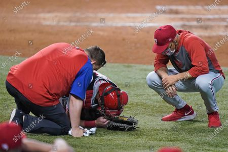 Trainer and Philadelphia Phillies manager Joe Girardi, right, check on catcher Andrew Knapp after Knapp was hit by a pitch during the third inning of a baseball game against the Miami Marlins, in Miami