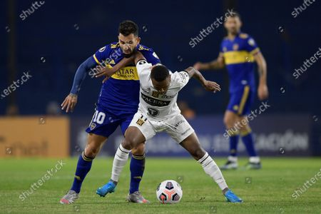 Stock Image of Carlos Tevez of Argentina's Boca Juniors, left, and Raul Castro of Bolivia's The Strongest battle for the ball during a Copa Libertadores soccer match in Buenos Aires, Argentina