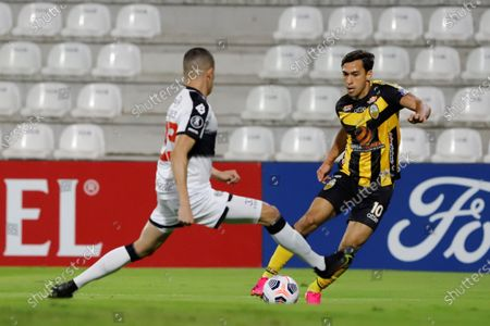 Stock Image of Braian Oscar Ojeda (L) of Olimpia in action against Michael O'Neal Covea (R) of Deportivo Tachira during the Copa Libertadores group B soccer match between Olimpia and Deportivo Tachira at the Manuel Ferreira Stadium, in Asuncion, Paraguay 26 May 2021.
