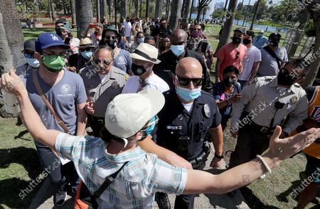 . Police officers escort L.A. City Councilman Mitch O'Farrell as he is heckled by homeless advocates and Echo Park residents upset with his decision to evict about 200 homeless people from the park earlier this year. The park reopened to the public on Wednesday, May 26, 2021. After its closure the park was cleaned and renovated. The evictions and closure remain a sore point for some. (Luis Sinco / Los Angeles Times)
