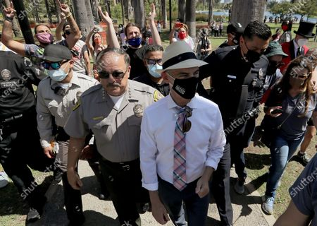 Stock Photo of . Police officers escort L.A. City Councilman Mitch O'Farrell as he is heckled by homeless advocates and Echo Park residents upset with his decision to evict about 200 homeless people from the park earlier this year. The park reopened to the public on Wednesday, May 26, 2021. After its closure the park was cleaned and renovated. The evictions and closure remain a sore point for some. (Luis Sinco / Los Angeles Times)