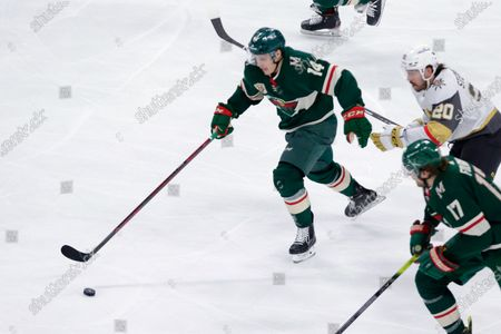Minnesota Wild center Joel Eriksson Ek (14) controls the puck in front of Vegas Golden Knights center Chandler Stephenson (20) and Wild left wing Marcus Foligno (17)) during the first period in Game 6 of an NHL hockey Stanley Cup first-round playoff series, in St. Paul, Minn