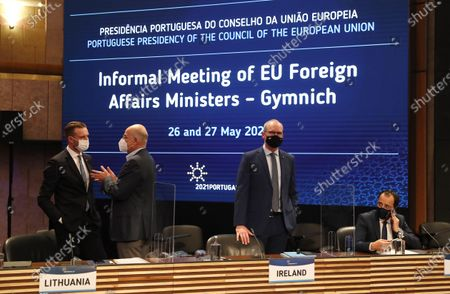 Ireland's Foreign Minister Simon Coveney, center, waits for the start of a round table meeting of EU foreign ministers in Lisbon, . European Union foreign ministers meet Thursday to discuss EU-Africa relations and Belarus
