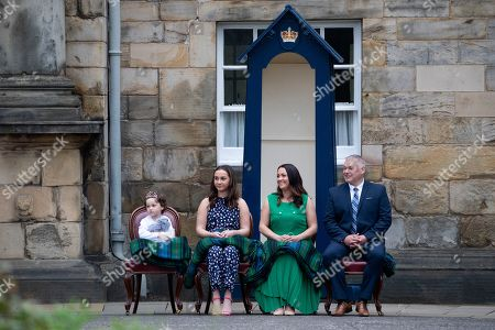 Mila Sneddon, 5, with her sister Jodi, and parents Lynda and Scott Sneddon, during the Beating of the Retreat, at the Palace of Holyroodhouse in Edinburgh. Cancer patient Mila features in an image from the Hold Still photography project which showed her kissing her father Scott through a window whilst she was shielding during her chemotherapy treatment