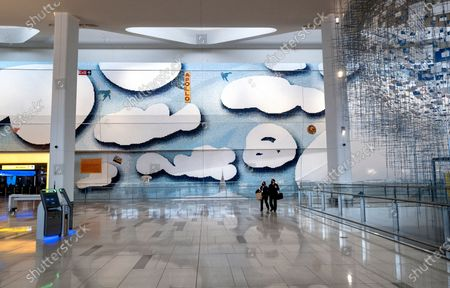 Stock Image of Pedestrians pass an art installation by Sarah Sze, right, and a mural depicting New York City themes by Laura Owens, that adorn the open areas of the recently opened Terminal B, at New York's LaGuardia Airport