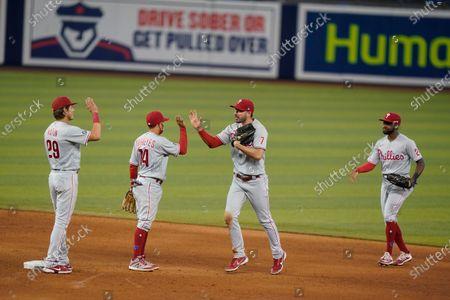 Philadelphia Phillies' Nick Maton (29) Ronald Torreyes (74) Matt Joyce (7) and Roman Quinn celebrate after the Phillies beat the Miami Marlins 3-2 during a baseball game, in Miami