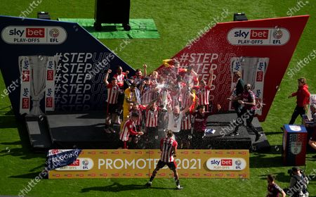 Pontus Jansson of Brentford celebrates &  lifts the play off trophy after victory as Ivan Toney of Brentford  sprays champagne (R) in celebration