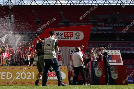 Sky Sports Betting and Gaming CEO Steve Birch hands the trophy over to Pontus Jansson of Brentford as players begin to celebrate