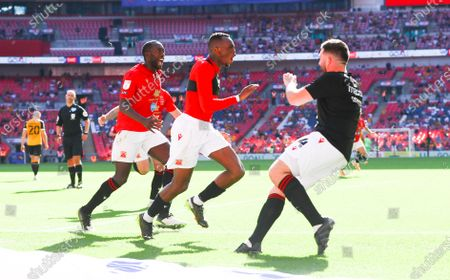 Carlos Mendes Gomes of Morecambe (centre) scores from the penalty spot past Tom King of Newport County in extra time & celebrates with the subs