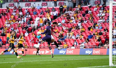 Tom King of Newport County saves ahead of Cole Stockton of Morecambe