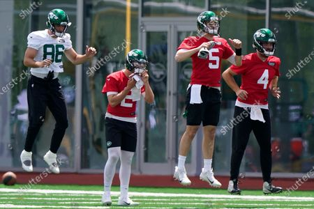 New York Jets tight end Ryan Griffin, (86), joins quarterbacks Mike White (5) and James Morgan (4) in a jumping drill as quarterback Zach Wilson (2), pauses to wipe his face with a towel during NFL football practice, in Florham Park, N.J