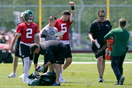 Quarterbacks Zach Wilson (2) and Mike White (5) take a break as offensive coordinator Mike LaFleur shouts out instructions during a break in an NFL football practice, in Florham Park, N.J