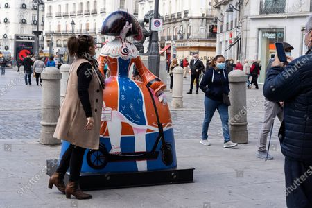 Stock Photo of People observe the figure of one of the 'Meninas', based on the 1656 painting by Diego Velazquez in the Prado Museum in Madrid, Spain, on November 02, 2020. The Sculptures of the Meninas, decorated by various celebrities, have been placed around the city and will be on display for a month as part of an outdoor street art exhibition.