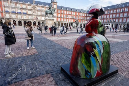 People observe the figure of one of the 'Meninas', based on the 1656 painting by Diego Velazquez in the Prado Museum in Madrid, Spain, on November 02, 2020. The Sculptures of the Meninas, decorated by various celebrities, have been placed around the city and will be on display for a month as part of an outdoor street art exhibition.