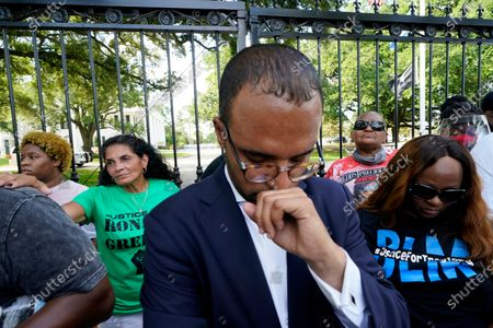 Stock Photo of Mona Hardin, background left in green, mother of Ronald Greene, prays outside the gates of the governor's mansion in Baton Rouge, La., protesting the death of Greene, who died in the custody of Louisiana State Police in 2019. Foreground is Ron Haley, attorney for the Greene family