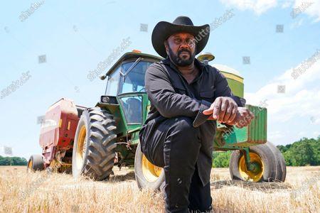 Farmer John Boyd Jr., poses in front of his hay bailer at his farm in Boydton, Va