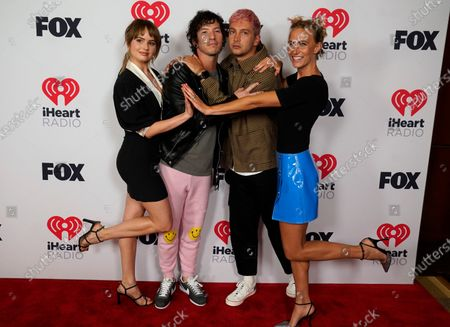 Josh Dun, center left, and Tyler Joseph, center right, of Twenty One Pilots, pose with Debby Ryan, left, and Jenna Joseph, right, at the iHeartRadio Music Awards at the Dolby Theatre, in Los Angeles