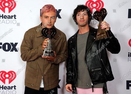 """Tyler Joseph, left, and Josh Dun, of Twenty One Pilots, pose with the awards for alternative rock song of the year for """"Level of Concern"""" and alternative rock artist of the year at the iHeartRadio Music Awards at the Dolby Theatre, in Los Angeles"""