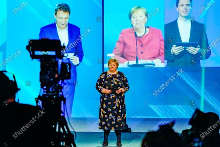 Stock Picture of Norwegian Prime Minister Erna Solberg and Chancellor Angela Merkel (on screen in the background) during the official opening of NordLink, the first power connection between Norway and Germany. NordLink is the first direct power connection between  the two countries, the high-voltage DC link enabeling the exchange of 1,400 megawatts, the output of almost one and a half conventional power plants.