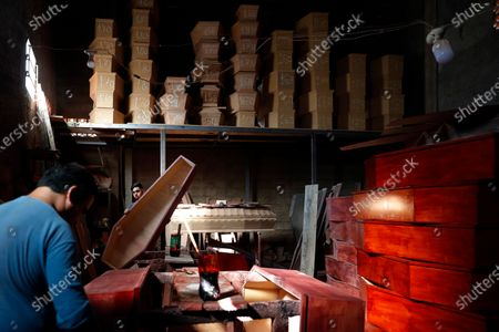Carpenters Orlando Vazquez, left, and Jonathan Fernandez, build coffins at the Shining Path coffin-making workshop during the COVID-19 pandemic in Asuncion, Paraguay, . The business has hired 50% more carpenters to keep up with demand during the pandemic
