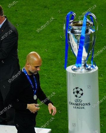Manchester City Manager Pep Guardiola looks dejected as he walks past the Champions League trophy