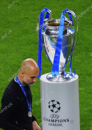 Stock Picture of Manchester City manager Pep Guardiola walks past trophy after defeat
