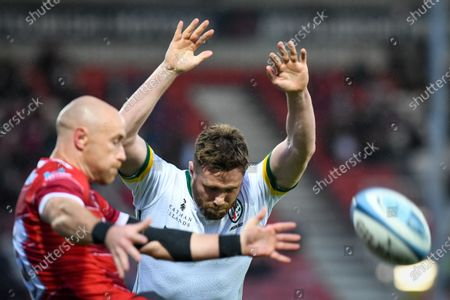 George Nott of London Irish attempts a charge down of Willi Heinz of Gloucester Rugby