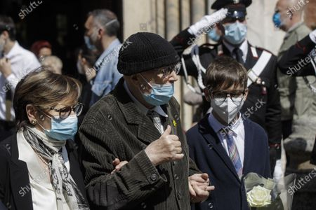 Beppe Menegatti, center, husband of Carla Fracci, walks off the church after the funeral service of his wife, outside San Marco church, in Milan, Italy, . Carla Fracci, an Italian cultural icon and former La Scala prima ballerina renowned for romantic roles alongside such greats as Rudolf Nureyev and Mikhail Baryshnikov, died Thursday at her home in Milan. She was 84