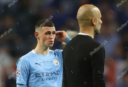Phil Foden (L) and manager Josep Guardiola of Manchester City react after the UEFA Champions League final between Manchester City and Chelsea FC in Porto, Portugal, 29 May 2021.