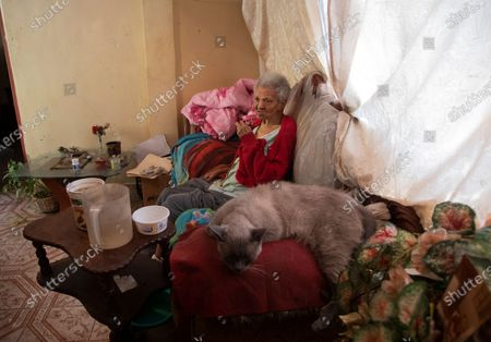 Zenobia Ansualve, 88, who lives alone, sits in her apartment after a home visit by Dr. Javier Manrique, in the Las Minas neighborhood of Caracas, Venezuela, . Manrique visits the elderly in their home as a way to help them from having to go out amid the new coronavirus pandemic