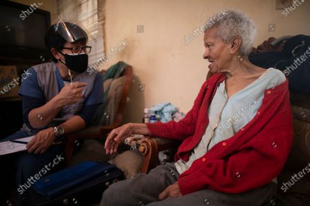 Stock Picture of Zenobia Ansualve, 88, who lives alone, talks with Dr. Javier Manrique during a home visit in the Las Minas neighborhood of Caracas, Venezuela, . Manrique visits the elderly in their home as a way to help them from having to go out amid the new coronavirus pandemic
