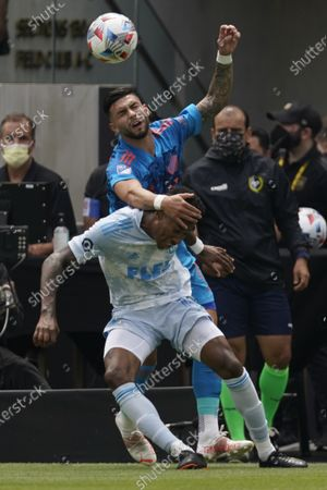 New York City FC midfielder Valentin Castellanos, back, and Los Angeles FC midfielder Mark-Anthony Kaye (14) collide during the first half of an MLS soccer game, in Los Angeles