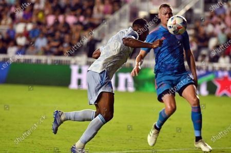 Stock Photo of United forward Ola Kamara, left, scores a goal as Inter Miami defender Ryan Shawcross closes in during the second half of an MLS soccer match in Fort Lauderdale, Fla