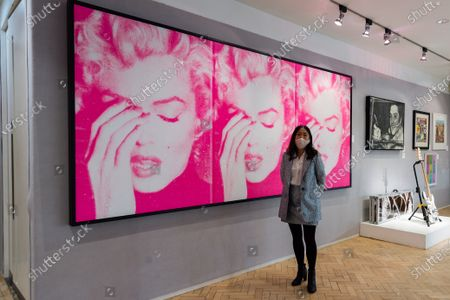 Stock Image of A gallery staff member stands next to Marilyn Crying (Triptych), 2011, by Russell Young (estimated sale price £50,000 - 70,000) during a photo call for Bonhams' Pop x Culture sale, on October 01, 2020 in London, England.