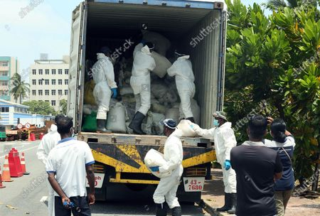 Stock Image of (210529) - COLOMBO, May 29, 2021 (Xinhua) - Sri Lankan security personnel load up a truck with debris from the X-Press Pearl ship in Colombo, Sri Lanka, on May 29, 2021. Sri Lankan Prime Minister Mahinda Rajapaksa on Saturday made an inspection visit to the coastal area in Uswetakeiyawa on the outskirts of capital Colombo which is affected by the debris washed up from the fire-ravaged container ship X-Press Pearl, the Prime Minister's Office said. During the inspection visit, the prime minister issued directives to the officials to expedite the provision of relief to the fishermen affected by the situation, a statement from the Prime Minister's Office said.