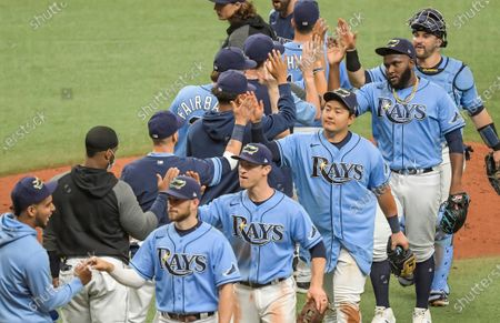 Stock Image of Tampa Bay Rays players, third from left to right, Brandon Lowe, Joey Wendle, Ji-Man Choi, Diego Castillo and Mike Zunino celebrate a win over the Philadelphia Phillies during a baseball game, in St. Petersburg, Fla