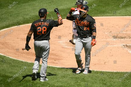 Baltimore Orioles' DJ Stewart (24) celebrates with teammate Pedro Severino (28) after hitting a solo home run during the third inning of a baseball game against the Chicago White Sox, in Chicago