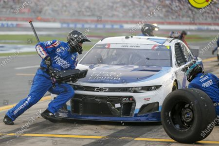 Brandon Johnson, left, jackman Kyle Larson, runs around the car during a pit stop under caution in a NASCAR Cup Series auto race at Charlotte Motor Speedway in Concord, N.C